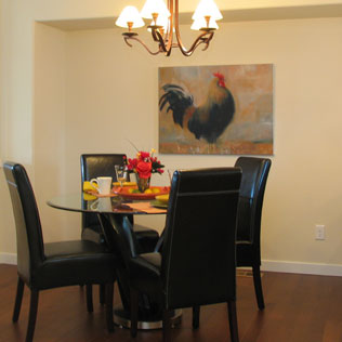 Image of a dining room with a rooster painting by Susie Buchanan