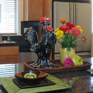 Image of a kitchen island staged by Susie Buchanan with a ceramic rooster and place setting